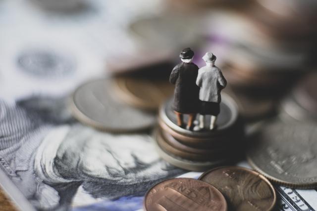 お金の上に立つ老夫婦