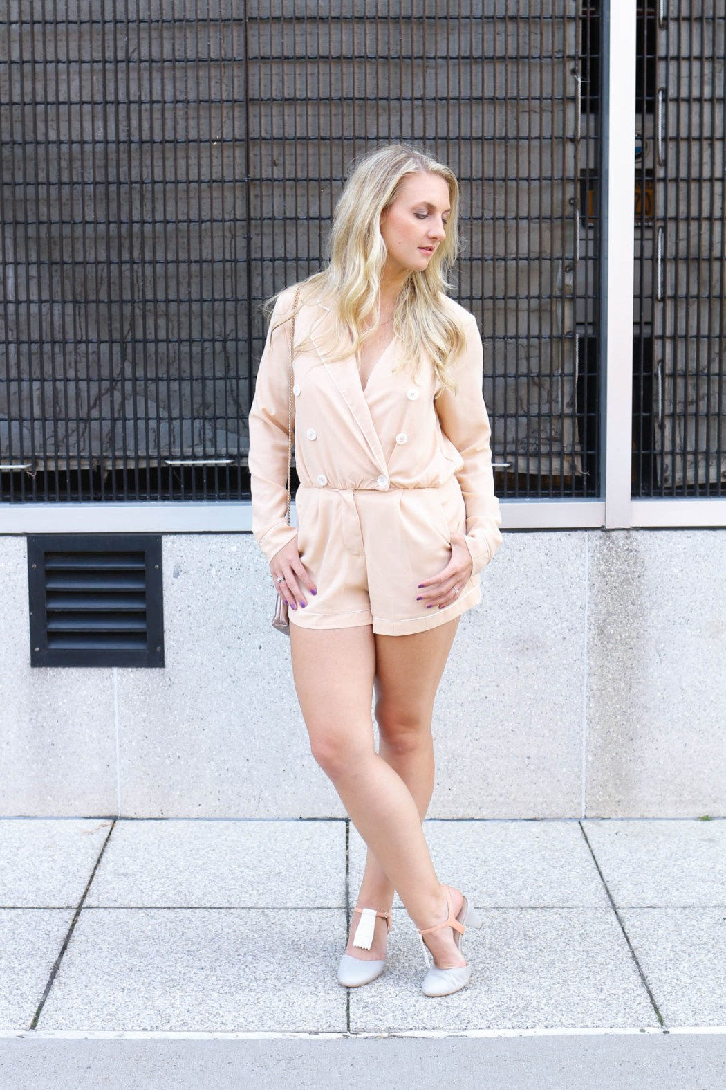 Fashion blogger Allyn Lewis of The Gem in a blush long sleeve romper with Drew & Co Jewelry and an Amazfit activity tracker.