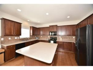Large kitchen with stained cabinets and island with room for seating.