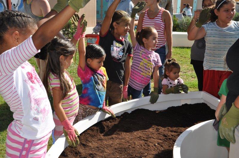 Children learning in a Kitchen Community modular garden.