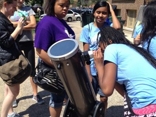 A girl from the near-west side of Chicago views the Sun safely through an Adler Planetarium telescope while four others look on..