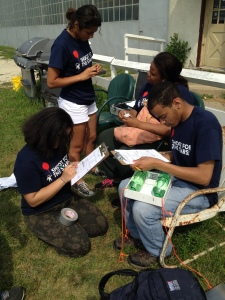 Four Science Leadership Corps students prepare their near-space science experiment for launch aboard a high-altitude balloon on August 1, 2014. In the image, two students are taking data on a clipboard, and two are preparing the experiment, which involves two bottles of soda.