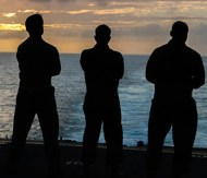 image of three men looking out over the ocean