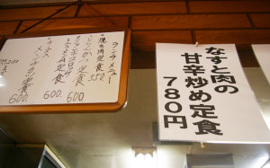 人気メニュー「なすと肉の甘辛炒め定食」や、お得なランチメニューの手書き看板