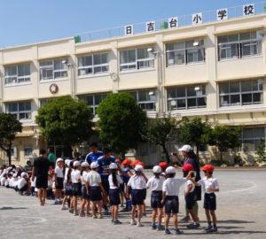 100名を越える児童らにハイタッチで見送られる2選手ら(日吉台小学校)