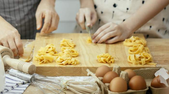Crop women making pasta nests with homemade dough