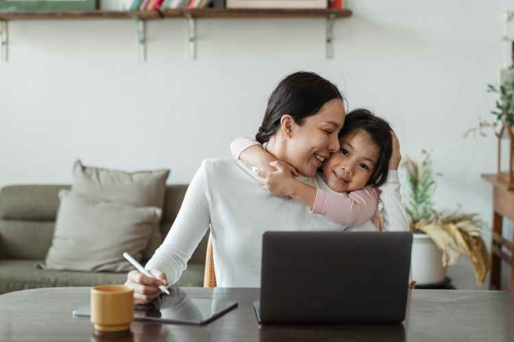 cute little ethnic girl embracing working mother