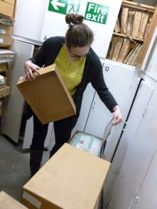 Juliette opening a box in the archive