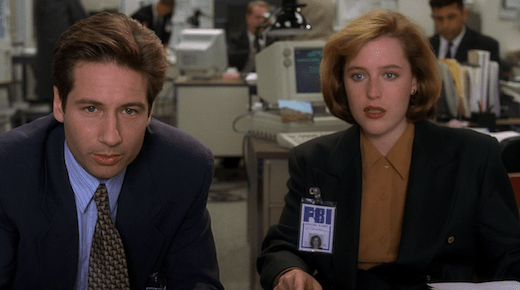 Mulder and Scully lean in to view evidence.