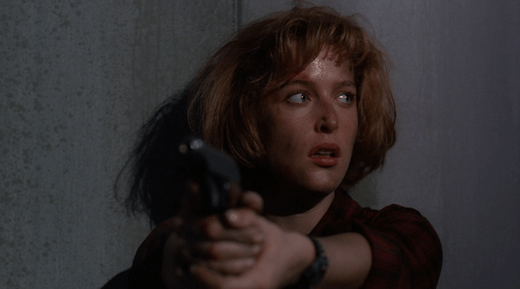 Scully keeps her gun trained on Peterson as she looks at Mulder.