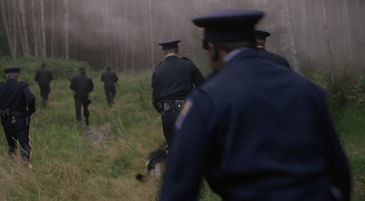 A group of police officers with guns and dogs hunt down the Jersey Devil.