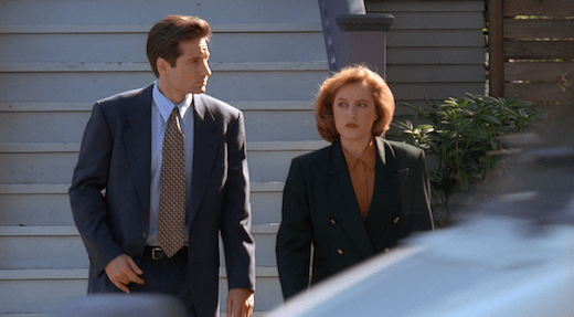 Mulder and Scully walk away from Lauren's house, both looking irritated.