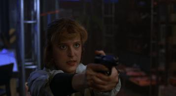 Scully points her gun at Mulder, her expression grim.