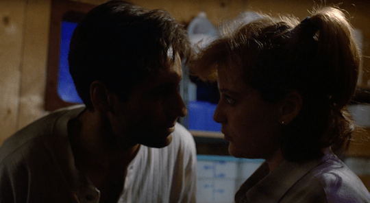 Mulder leans down to speak urgently to Scully.