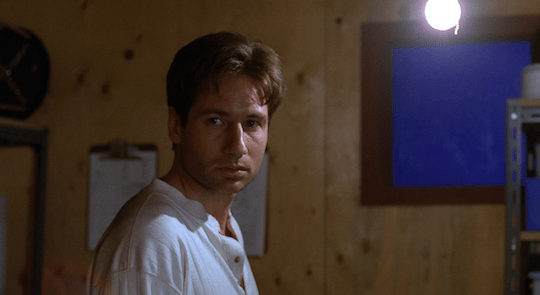 Mulder looks at Scully before she leaves him alone in a locked room.