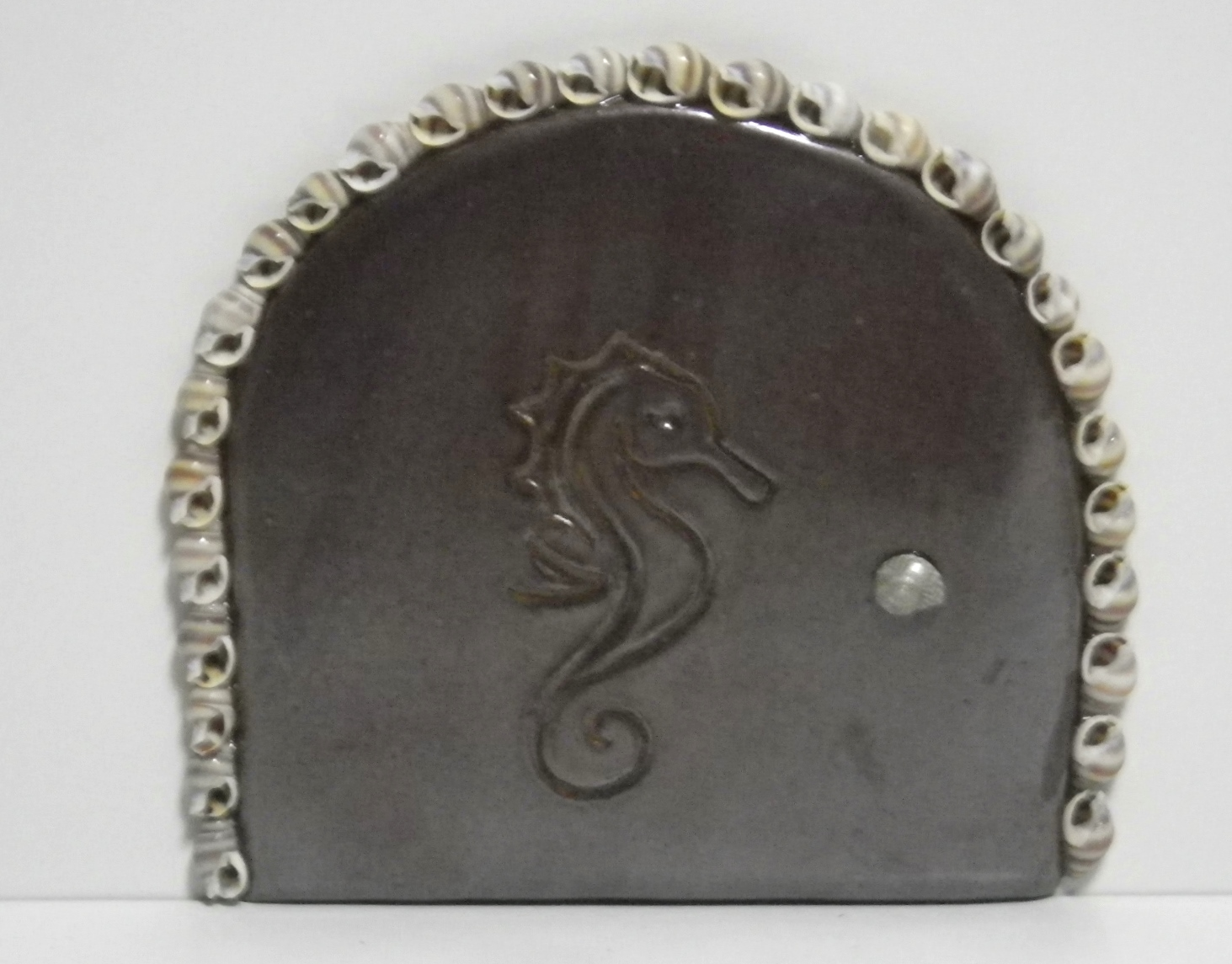 brown fairy door, embossed with a seahorse and embellished with seashells