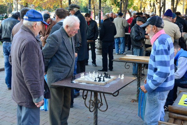 Old men playing chess in a park - a definite part of a big city