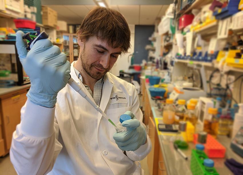 Un joven vestido con una bata de laboratorio pipetea líquido verde en un recipiente pequeño mientras está de pie en un laboratorio