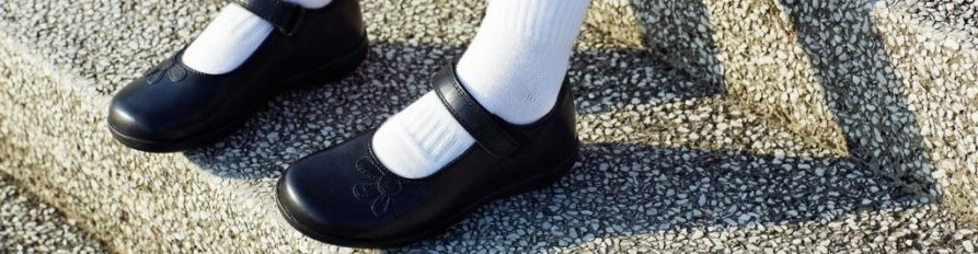 Girls feet in white shin-high socks and black Mary Jane style school shoes