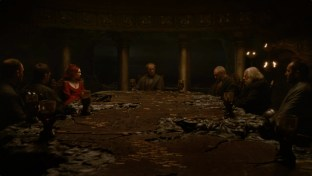Stannis sits at a poorly-lit table with his advisors.