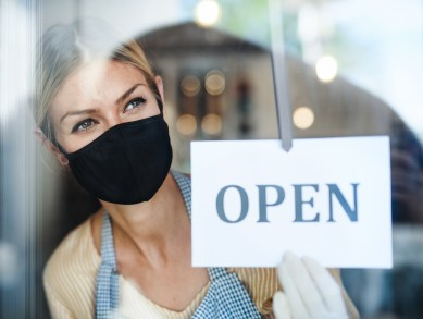 shop owner with mask and open sign