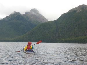 Zach kayaking in Southeast Alaska with red paddle and life preserver donated by Walt Roberts.