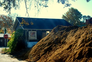 Our small, but quaint cottage peaking out behind the mounds of dirt and constant ground work.