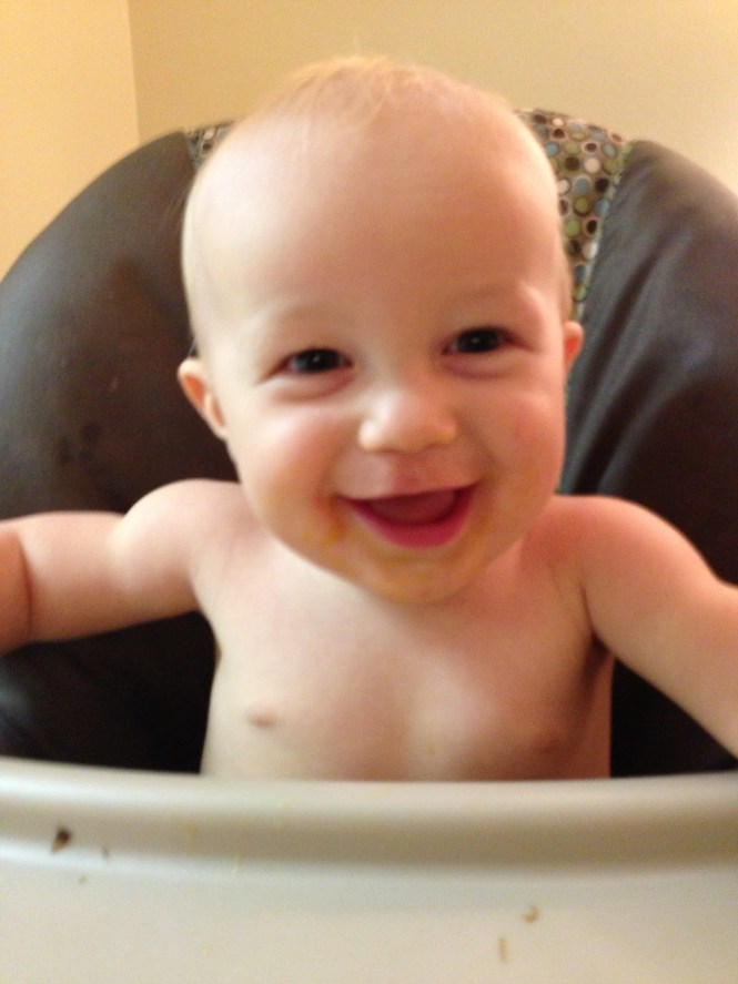 Shirtless baby in highchair