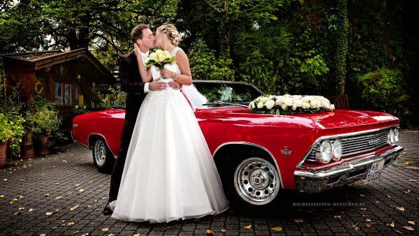 Brautpaar mit rotem Hochzeitsauto