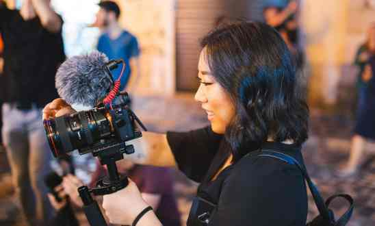Woman holding camera with microphone