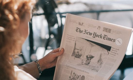 Looking over the shoulder of a female reading the New York Times