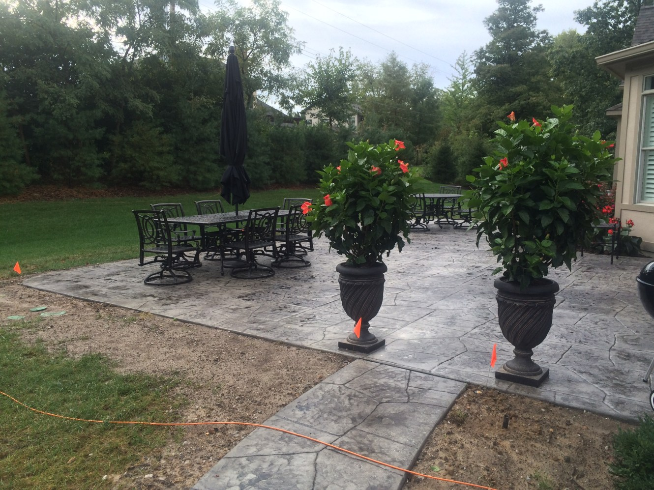 Grey Concrete Patio with Table, Chairs and Planters