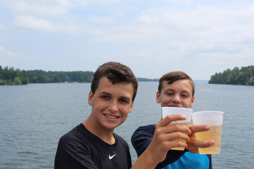 Parker and Apollo cheers the good life on the St. Lawrence River in Upstate NY.  Thousand Islands is one of the best things to do in upstate NY.