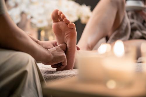 Woman enjoyingreflexology foot massage in wellness spa