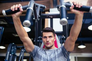 Portrait of a fitness man doing exercise on fitness machine in gym