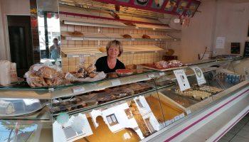 Eine Frau steht hinter dem Tresen in einem Bäckereigeschäft.