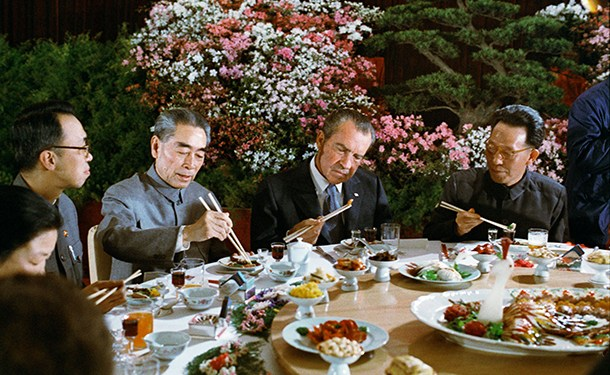 President Nixon gamely tries out his chopsticks at a banquet given in his honor