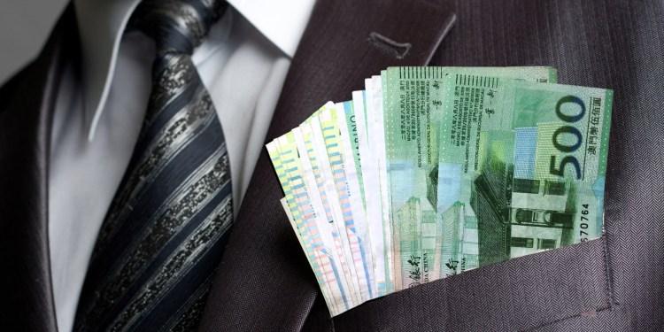 Formal weared businessman with earned money in suit pocket