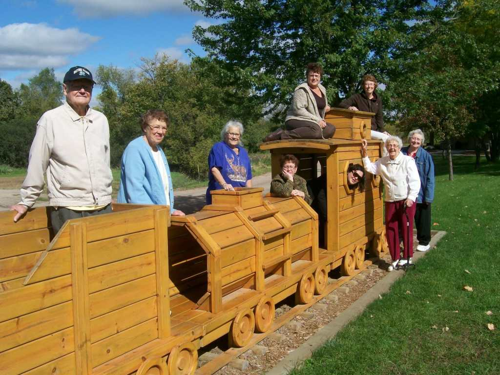 Nine elders on and near a large wooden train.