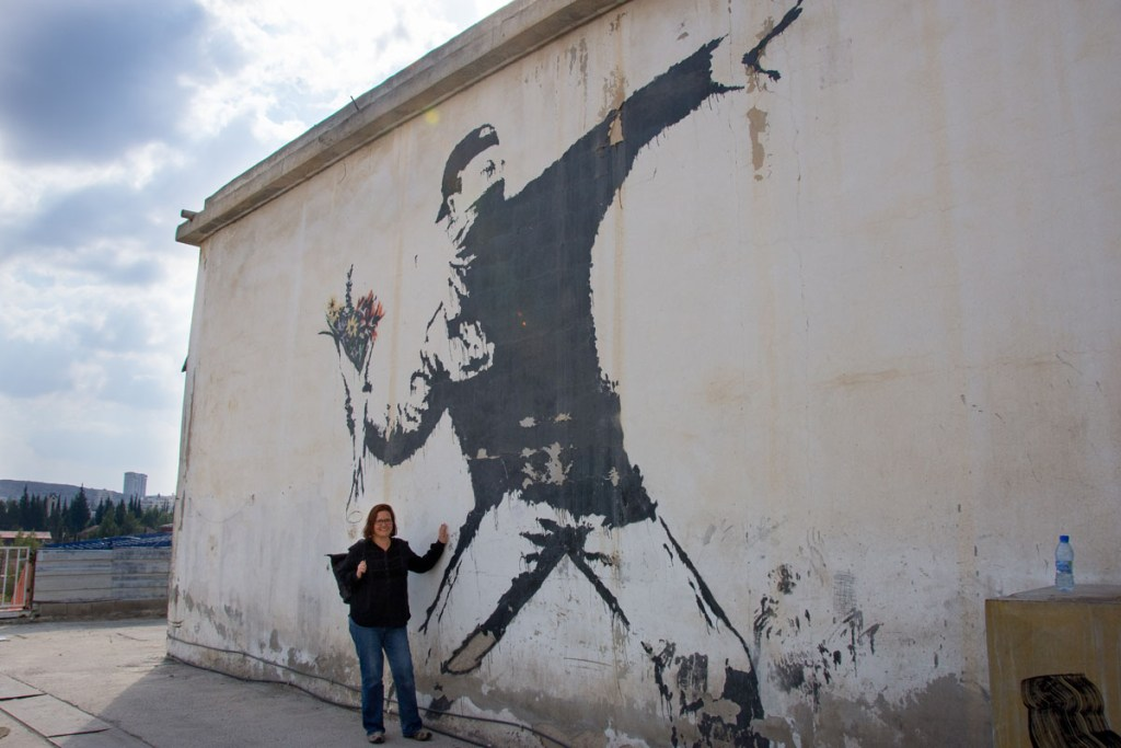 "Standing in front of the ""Flower Thrower"" Banksy mural"