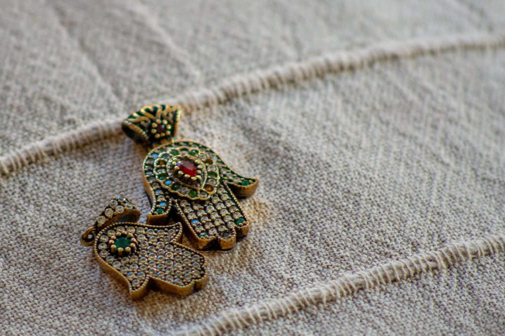 two silver hamza pendants
