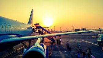 Plane sits on tarmac with sunset behind