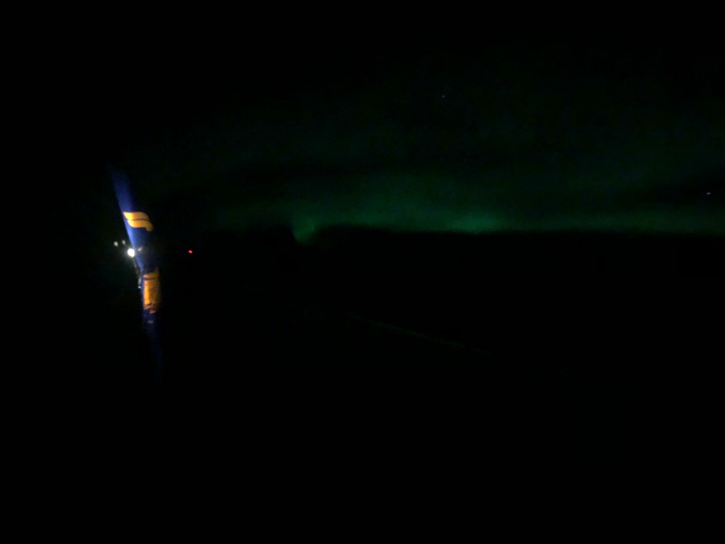 Green shimmers from the Northern Lights seen from Icelandair flight