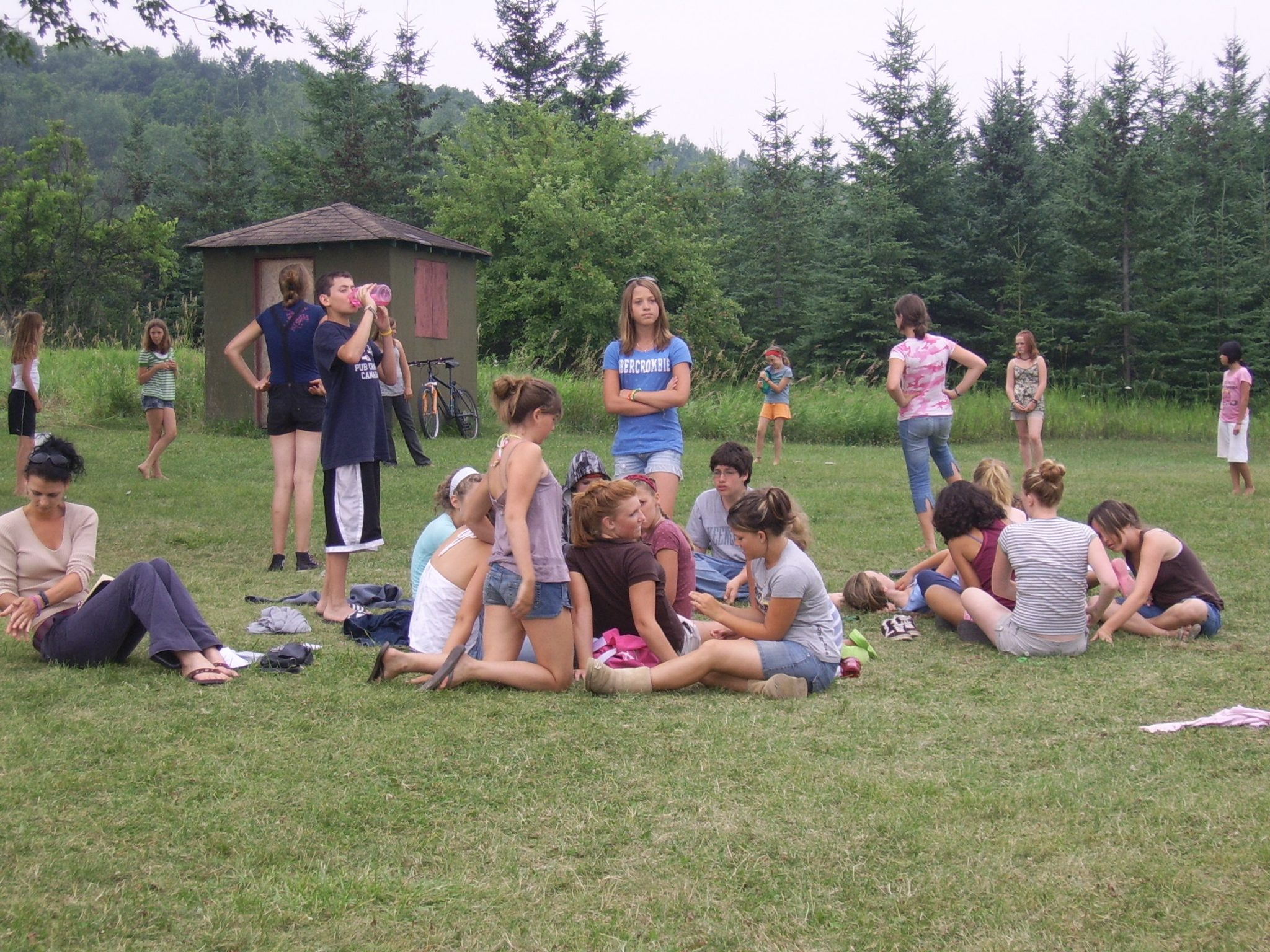 A group of campers hang out in The Hollows Camp field waiting for their next activity