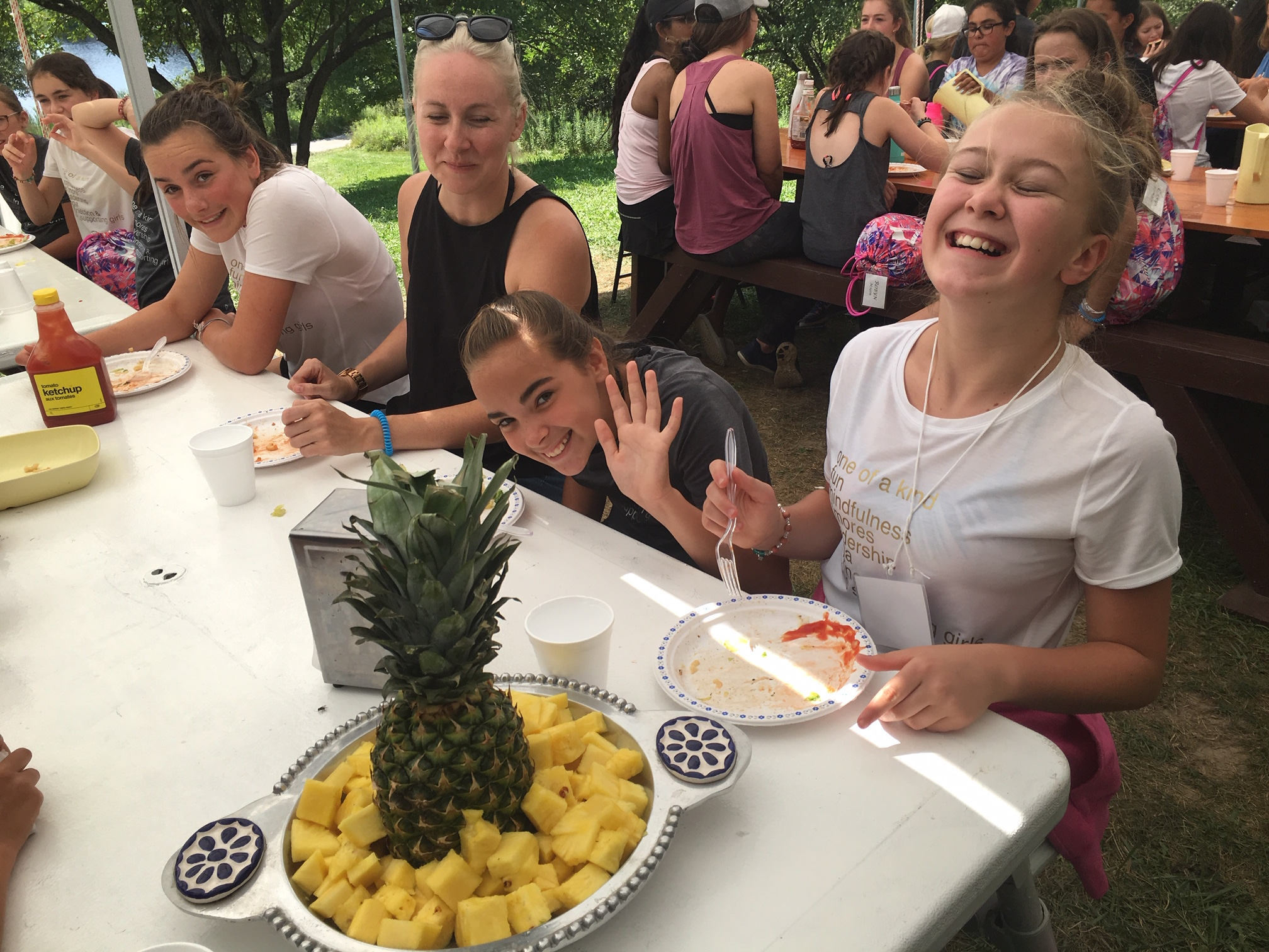 A group of girls eating a healthy pineapple and laughing under the outdoor lunch area at The Hollows Camp