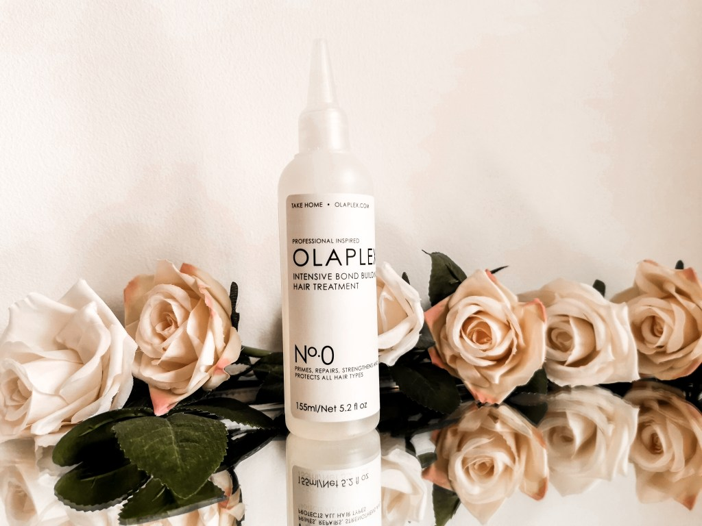 Bottle of Olaplex No.0 surrounded by flowers