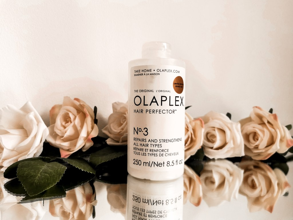 Bottle of Olaplex No.3 surrounded by flowers