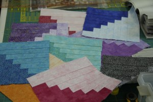 """Split Log Cabin with Shimmer - this student chose not to """"shuffle"""" the fabrics - I liked her colors so much that I am going to use Shimmer for Cabin Fever - call cut just need to start sewing!"""