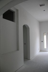 Standing under the large arch looking across the foyer to the front door just out of view on the left.  The opening in the top of the photo is for a stained glass window for the shower in the guest bathroom, I love how they framed the area below - I have lots of ideas for that space.