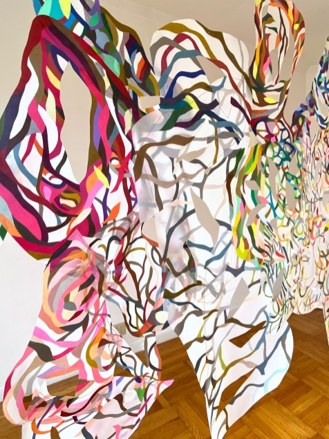 """Spiral Dance,"" (Detail 3) Colored Pencil on Drafting Film with Sewing suspended with monofilament wire, 9'H x 12.5'W. 2020."